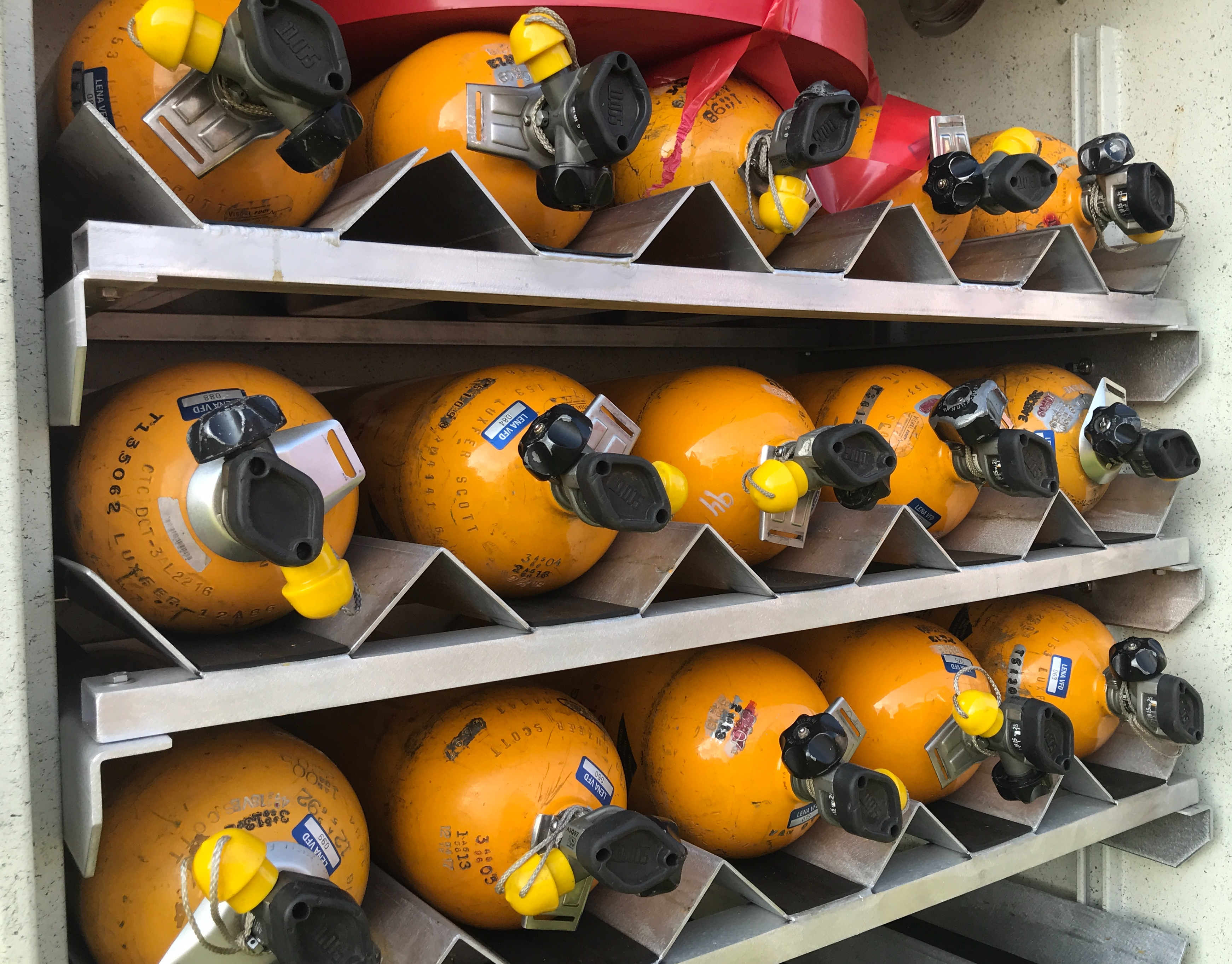 Portable breathing apparatuses line a compartment in a Lena Fire Department truck.