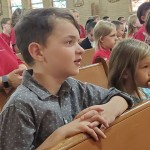 Third grade student Colton Farley, left, and first grade student Ayriss Nicholas pray as they partake in the first all-school Mass during the new school year at Sacred Heart Catholic School.  Contributed