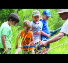 Matthew Briggs, left, August Yogow, Evan Rankin and Jeremiah Hodges survey the bugs, tadpoles and other pond life in a net shared by Navarino Nature Center naturalist Tim Ewing.  Carol Ryczek | NEW Media