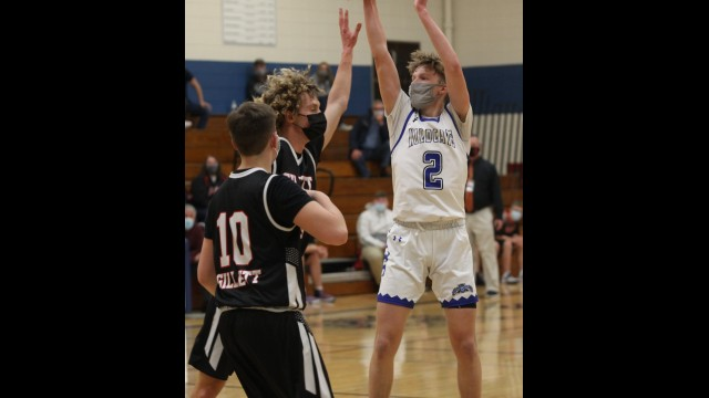 Lena's Max Beyer hits a jumper late in the second half while being defended by Gillett's Evan Peterson, center, and Devin Waranka in a Marinette & Oconto Conference matchup on Jan. 8 in Lena.  Morgan Rode   NEW Media