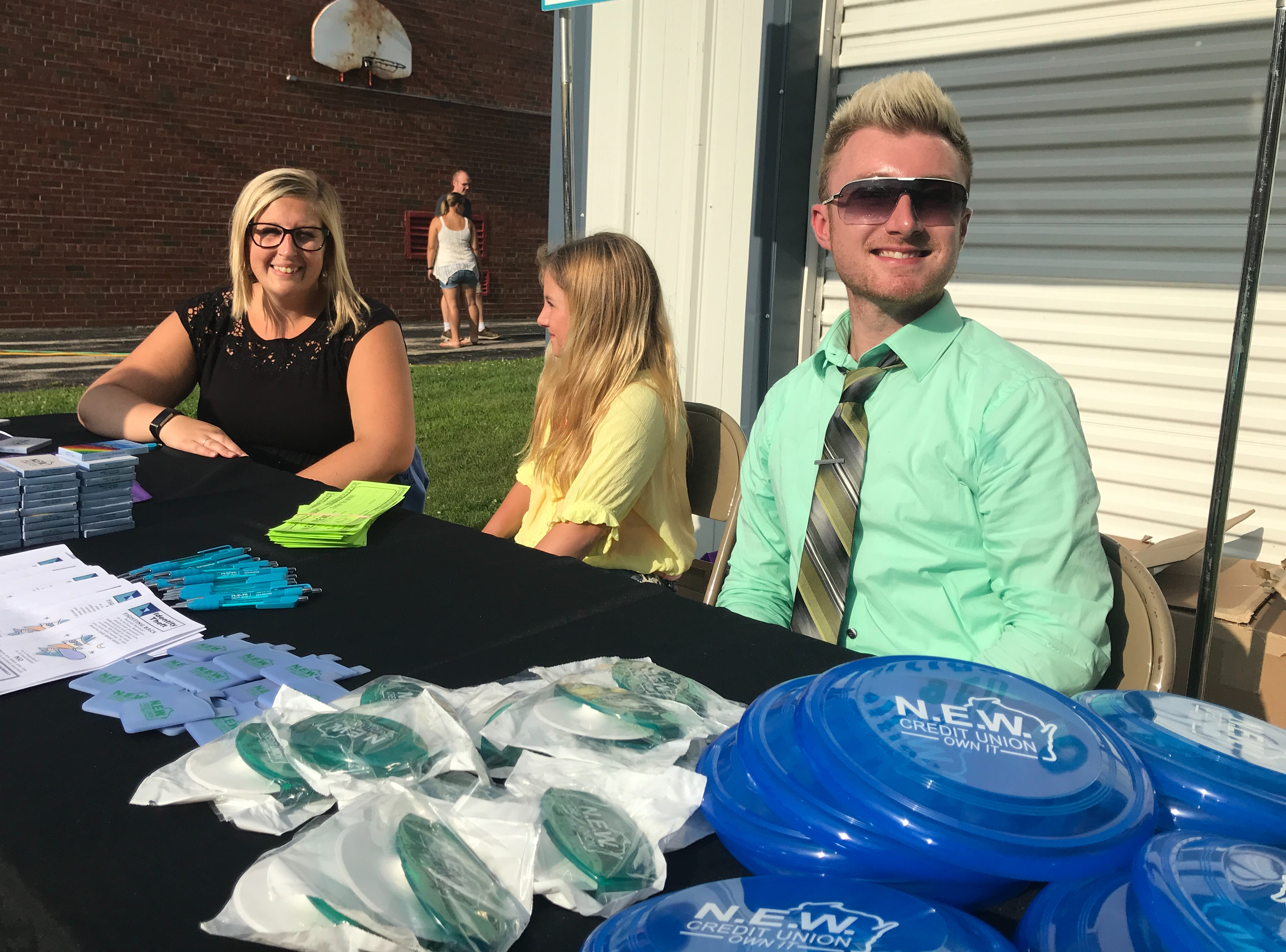 Savannah Thomson and Tyler Dolata of NEW Credit Union help National Night Out visitors learn more about protections against identity theft.