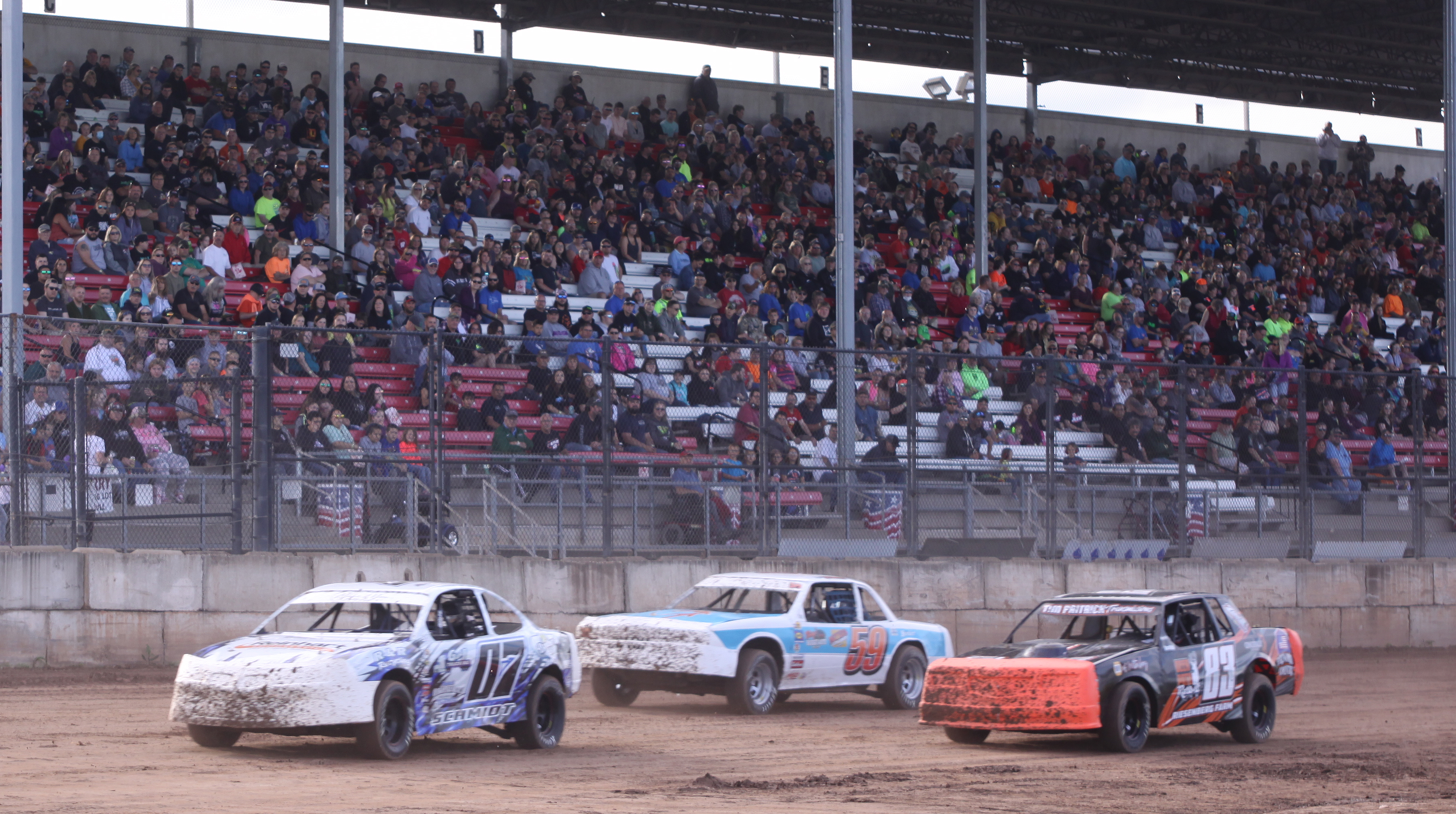 Mike Schmidt (7), Larry Buckwheat (59) and Cody Scray (83) compete in a IMCA Stock Car heat race in front of the Shawano Speedway grandstand during Saturday&#039;s season opener.<br />Morgan Rode | NEW Media