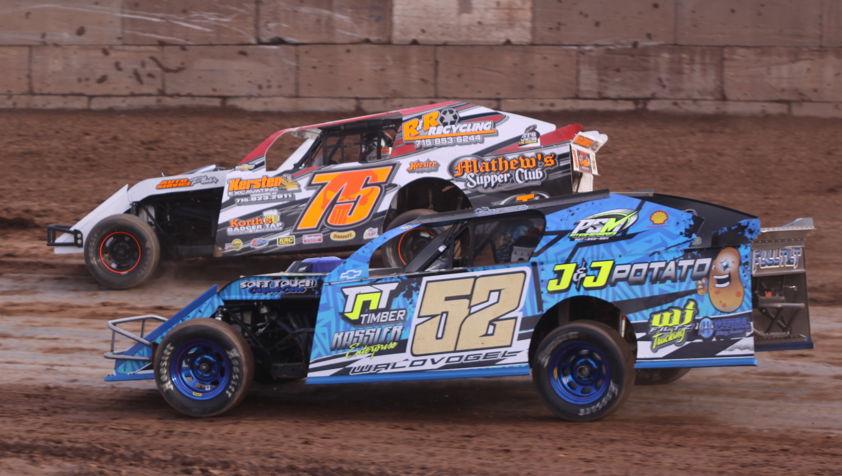Max Oreskovich (75) and Dylon Waldvogel (52) round a turn during an IMCA Sport Mod heat race during Saturday&#039;s season opener at Shawano Speedway.<br />Morgan Rode | NEW Media