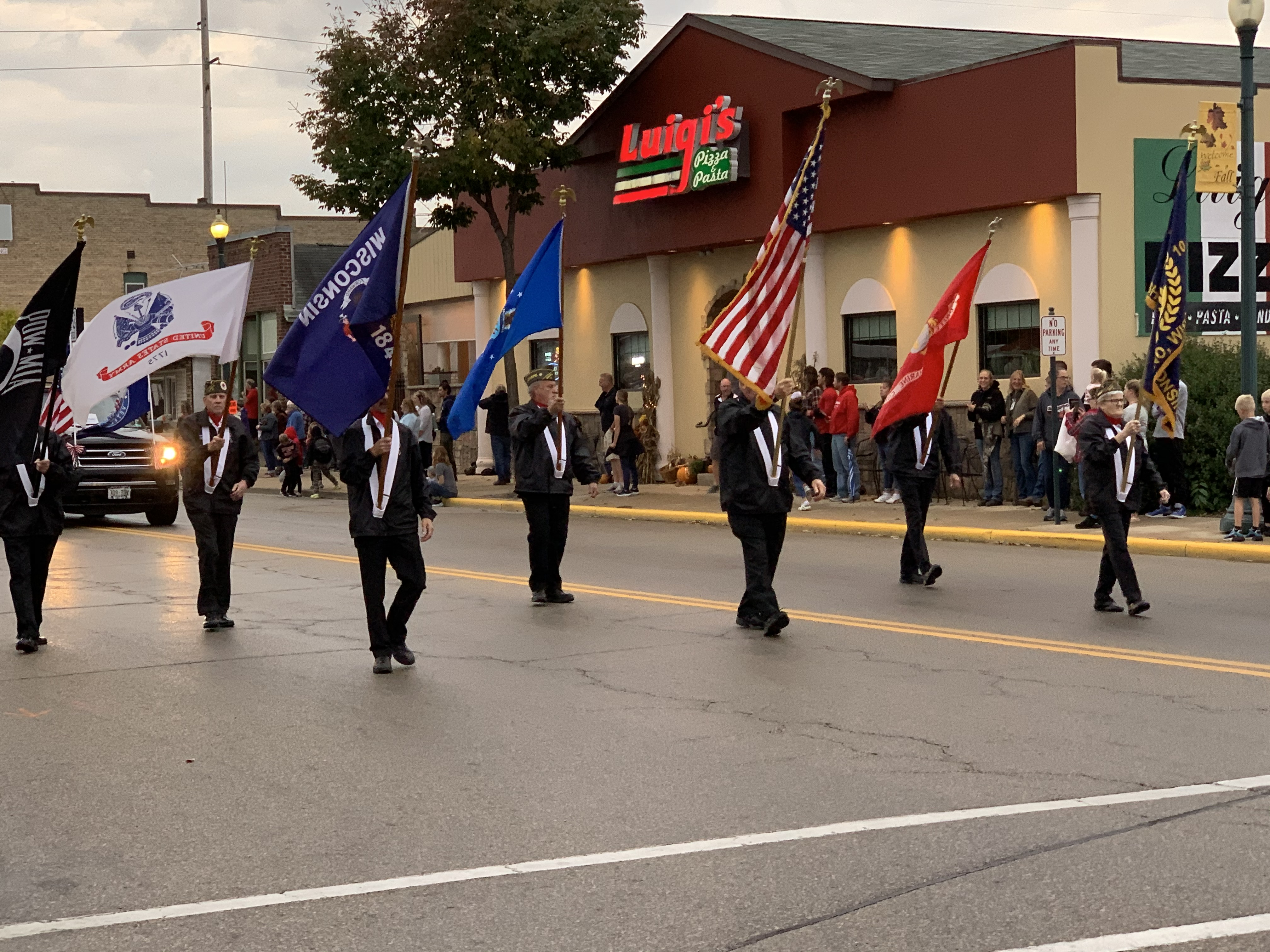 The American flag is prominently flown next to other flags as veterans lead the march of the homecoming parade in Shawano on Sept. 24.Luke Reimer   NEW Media