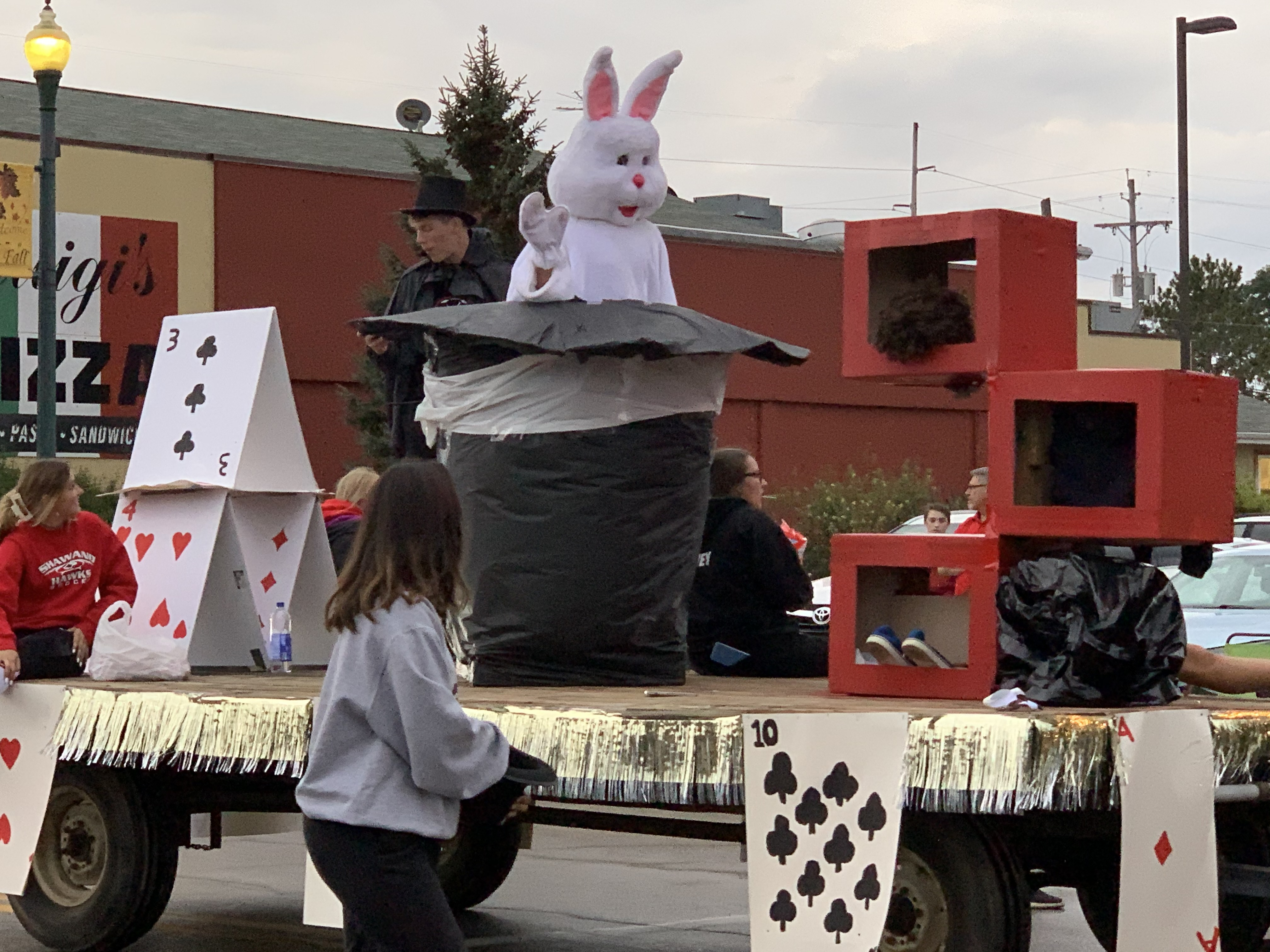 """To fit with the theme of """"magic happens,"""" a float travels down Main Street featuring playing cards and a human-sized rabbit coming out of a top hat during the homecoming parade on Sept. 24.Luke Reimer   NEW Media"""