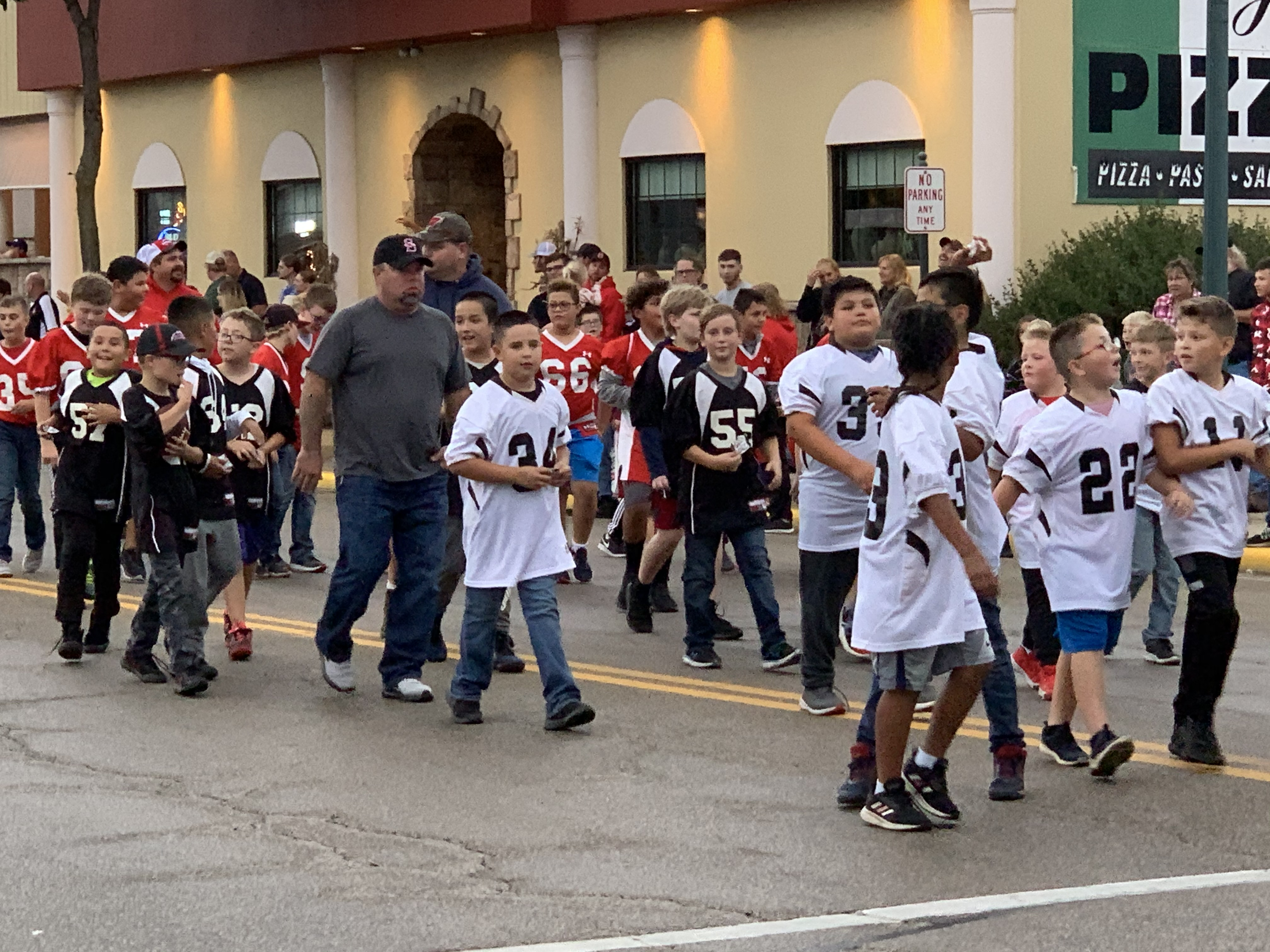 Children involved with youth football get their chance to wave to Shawano visitors as they walk down Main Street during the homecoming parade on Sept. 24.Luke Reimer   NEW Media