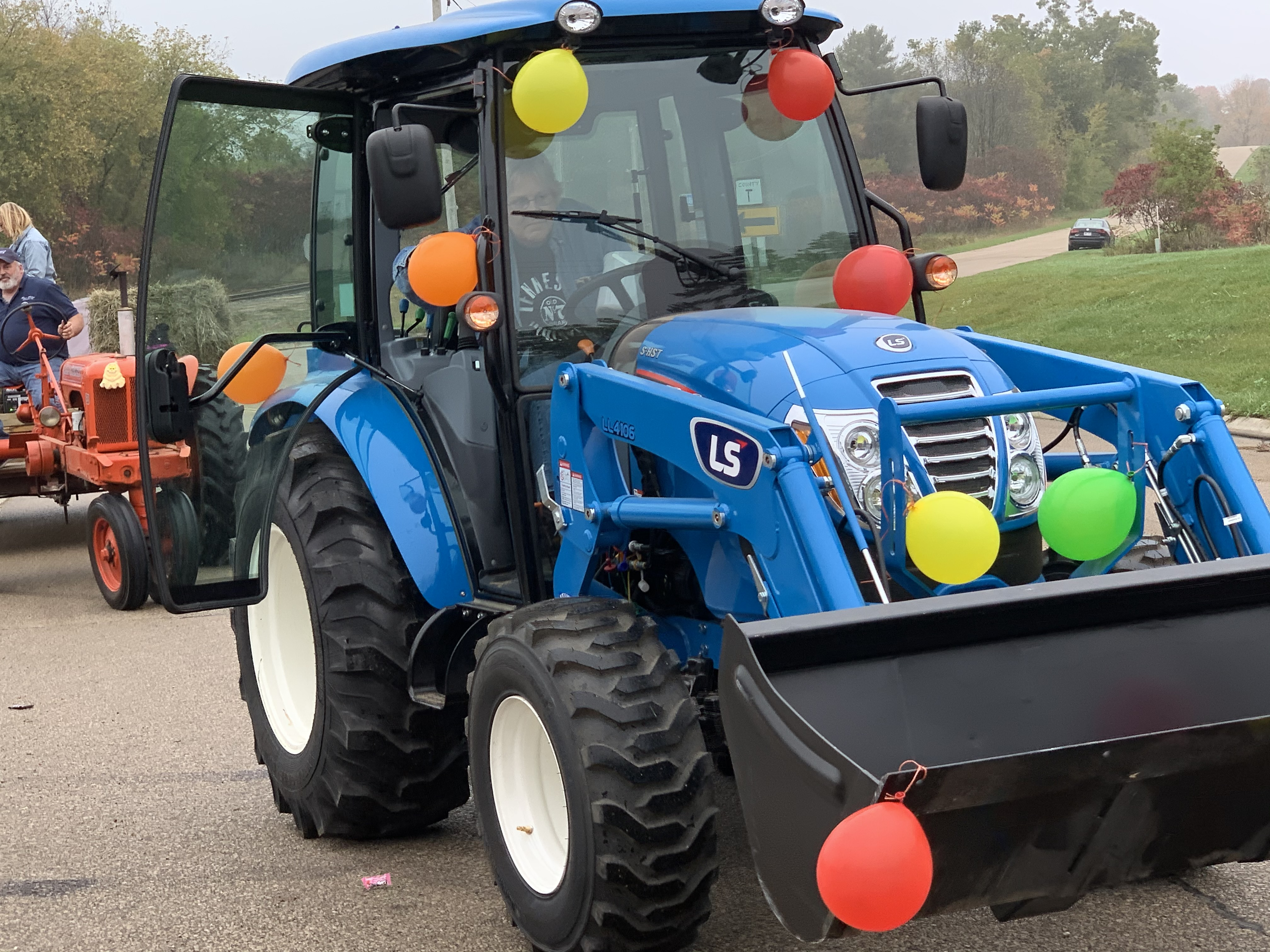A blue tractor decorated with balloons rolls down County Road T in Lunds, part of the Bohemian Fest parade Oct. 9.Luke Reimer | NEW Media