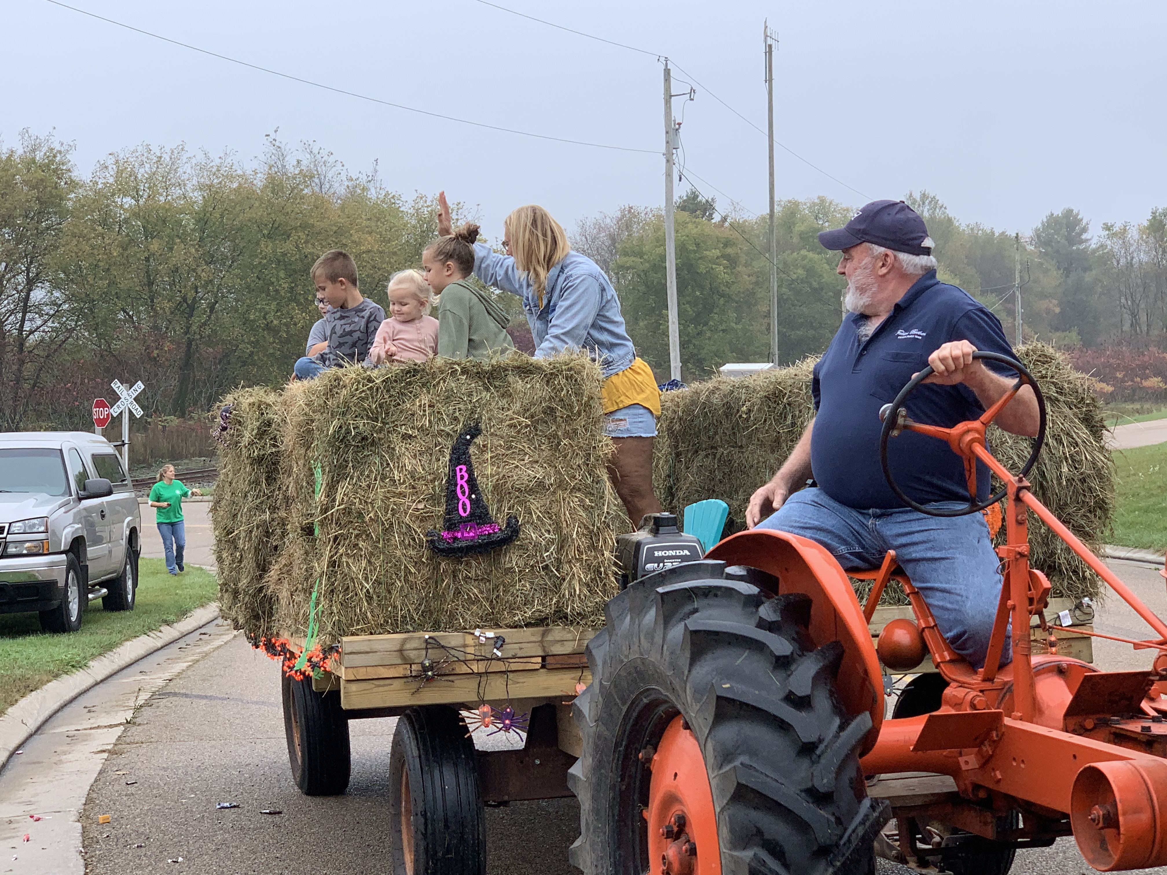 Children ride on hay bales behind a tractor as they wave to visitors and throw candy on County Road T in Lunds on Oct. 9.Luke Reimer | NEW Media