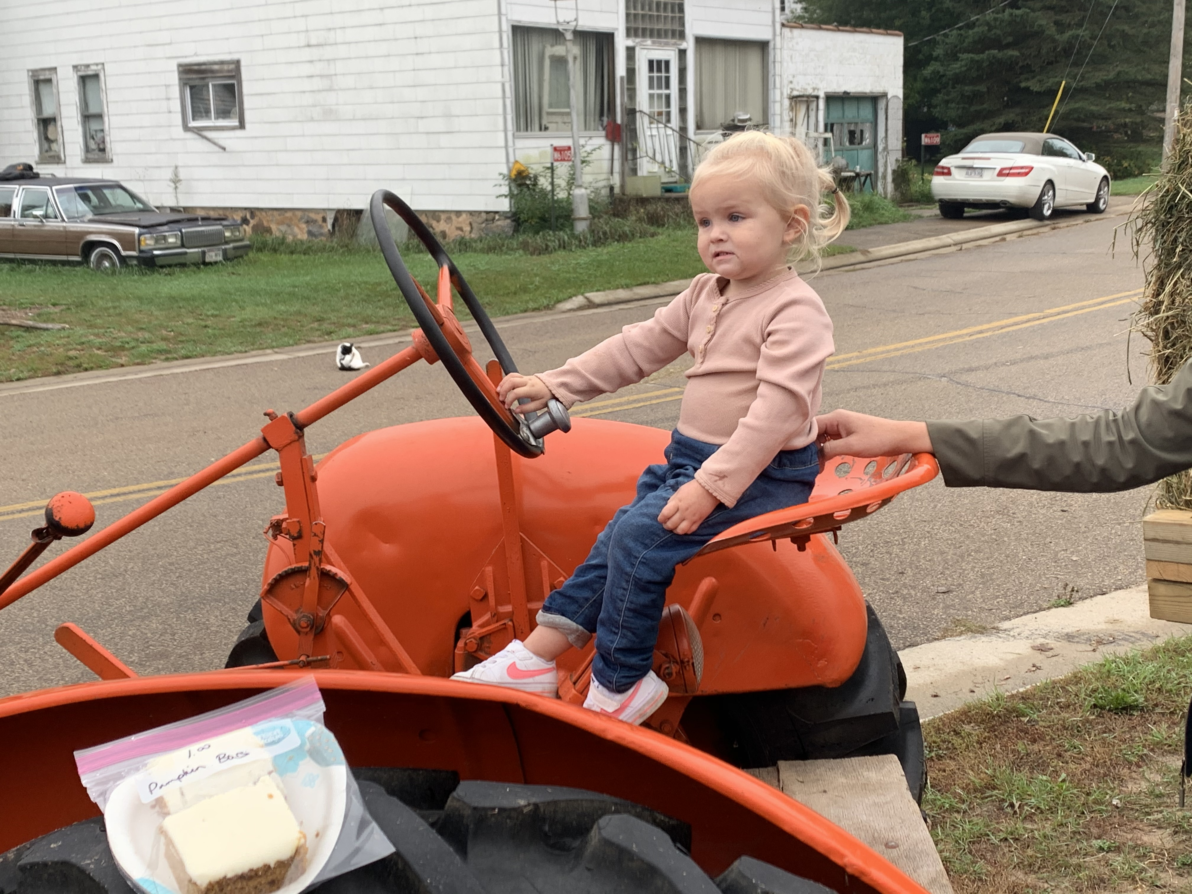Shawano resident Noella Coe sits in the driver seat of a tractor, pretending that she is driving down the street at Bohemian Fest on Oct. 9 in Lunds. The event included a parade and lunch.Luke Reimer | NEW Media