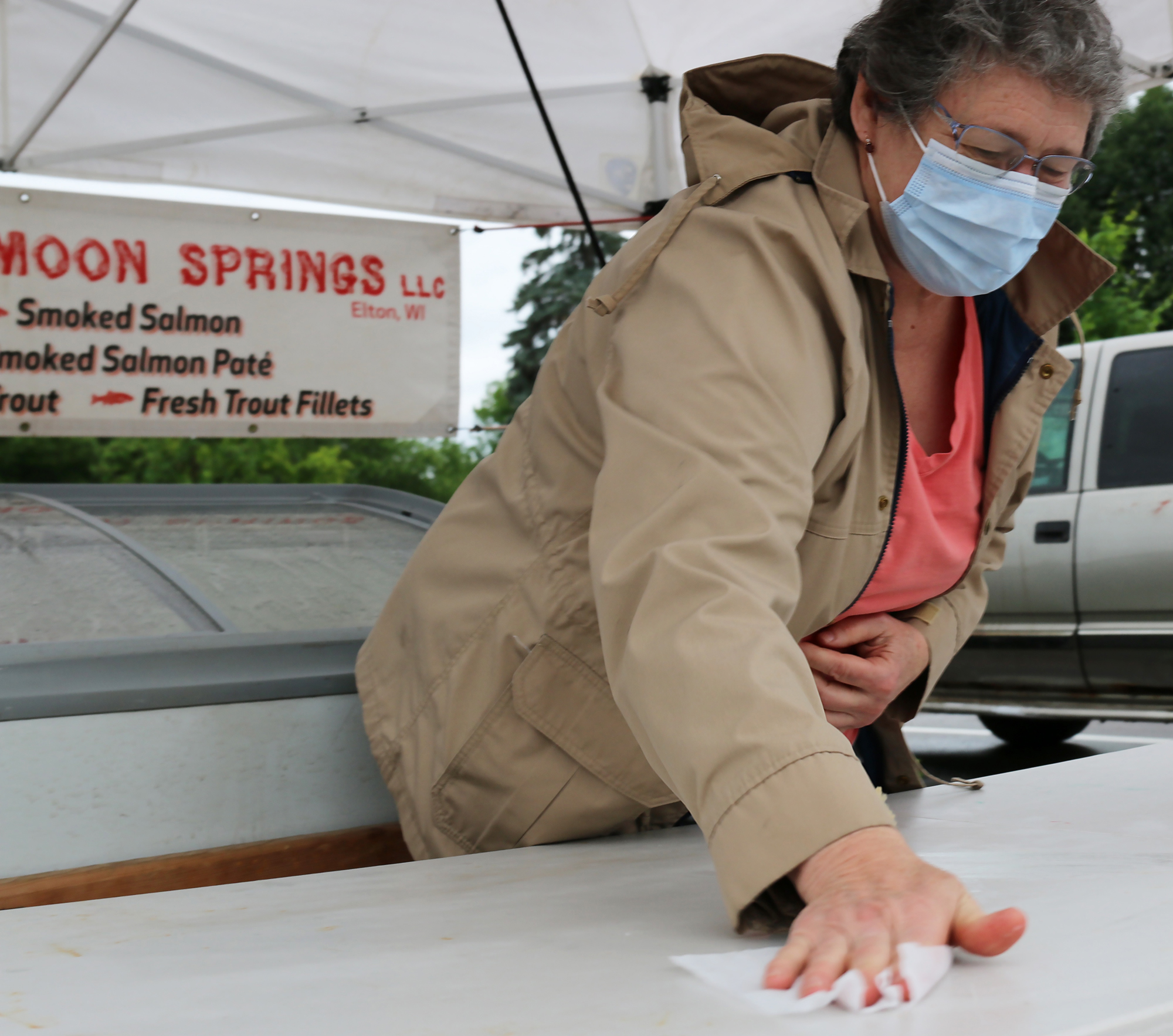 Bobbie Schneider of Silver Moon Springs wipes down her table after each customer at the first FRESH Project Farmers Market on Saturday. Most vendors wore masks and wiped down surfaces. Social distancing was not too much of an issue, given the repeated rain showers that limited the crowds.Carol Ryczek   NEW Media