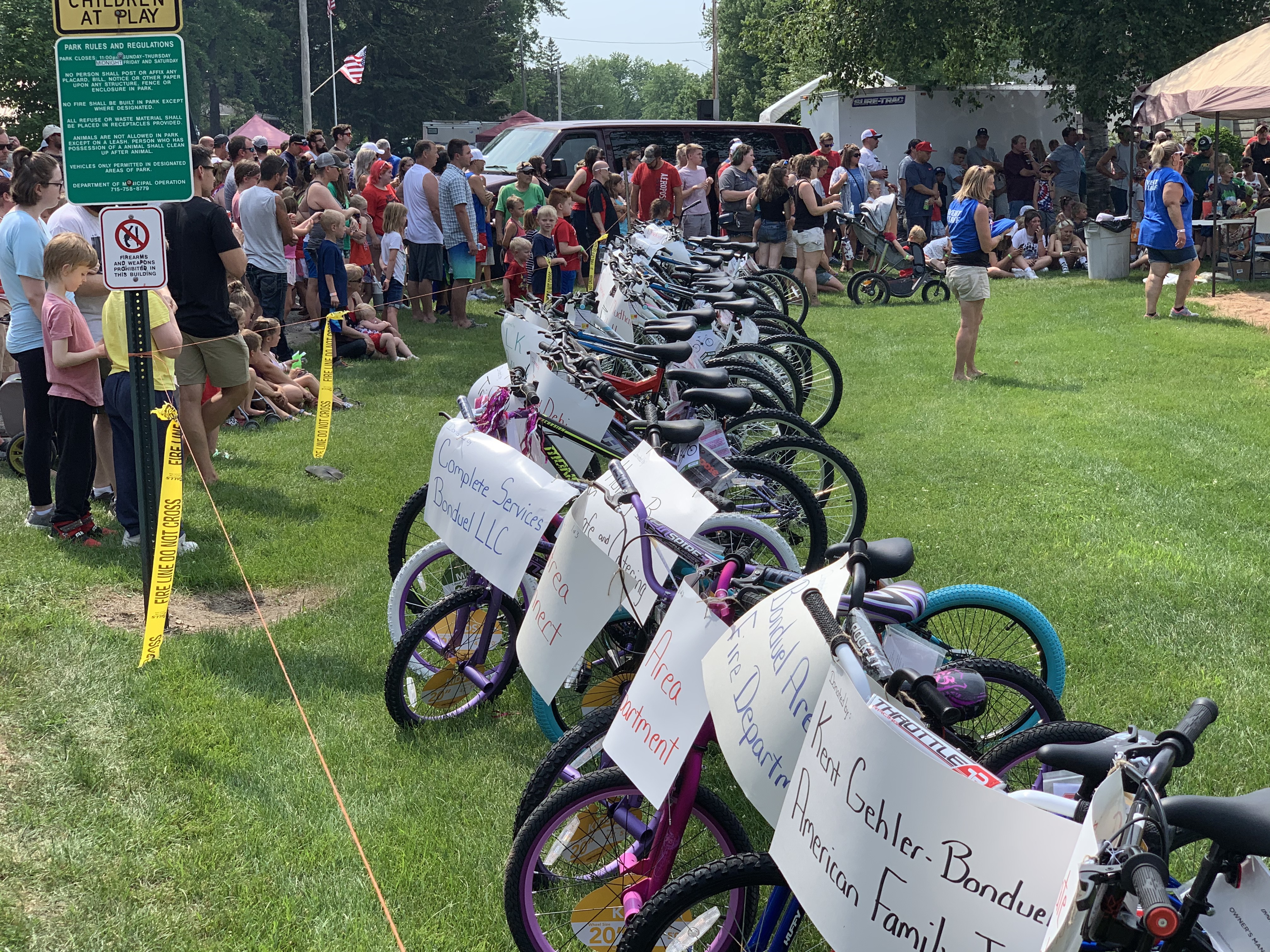 Visitors wait in anticipation of the bike raffle July 4 at Village Park in Bonduel. More than 100 bikes were donated for families to win at the event.Luke Reimer   NEW Media