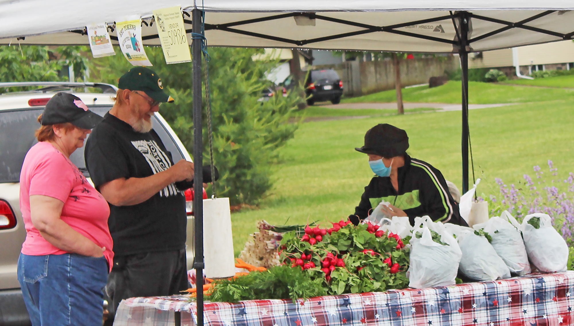 """Jolene and Peter Daniel, left, complete a purchase from Zoua Lee, right, on June 20 at the season's first Shawano Farmers Market at Franklin Park. Although the couple was called """"diehards"""" by another vendor, Peter said, """"I just like all of the fresh veggies."""" The farmers market will take place every Saturday through Oct. 3.David Wilhelms"""