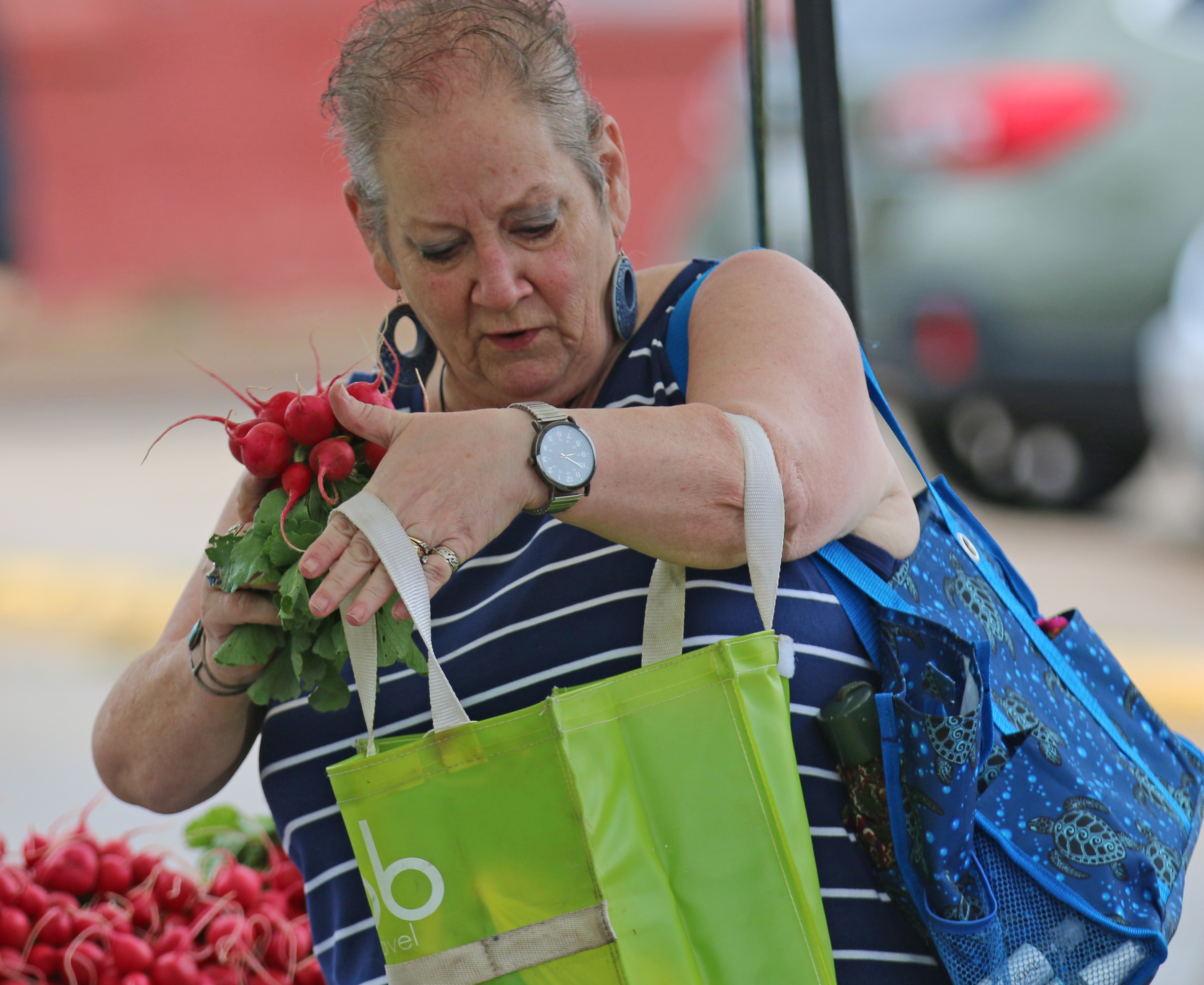 Cindy Keuschel, a Loon Lake resident, selects radishes at the first Farmers Market of 2020 in Shawano. The market had regular attendees, according to the FRESH Project, new organizers of the market, despite the regular downpours Saturday morning.Carol Ryczek   NEW Media
