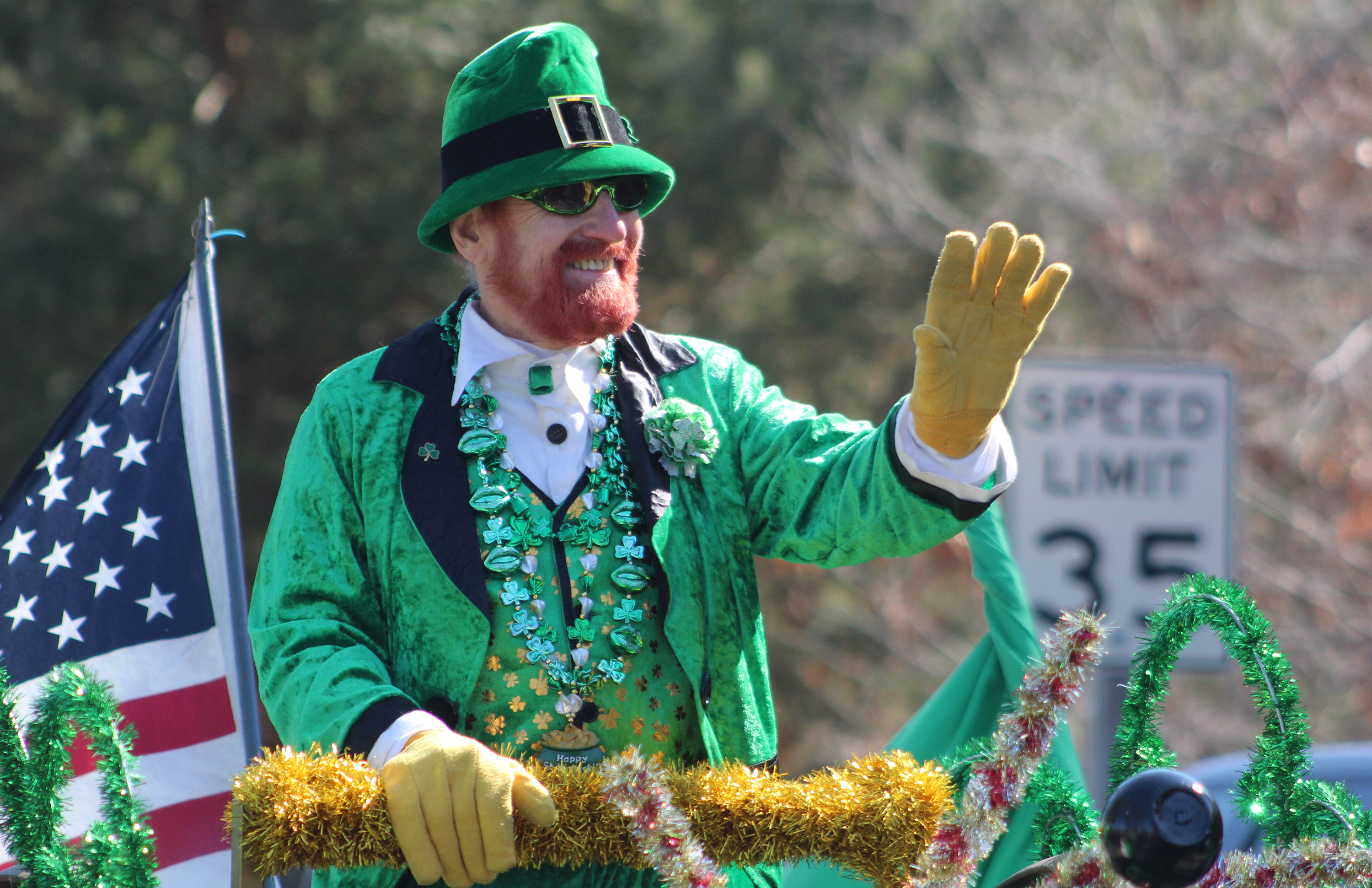 Jim Starks, grand marshal for the Mooseyard St. Patrick's Day parade, waves to onlookers as his float passes by near the beginning of the parade. There were plenty of people donning green for the annual event.(Lee Pulaski | NEW Media)