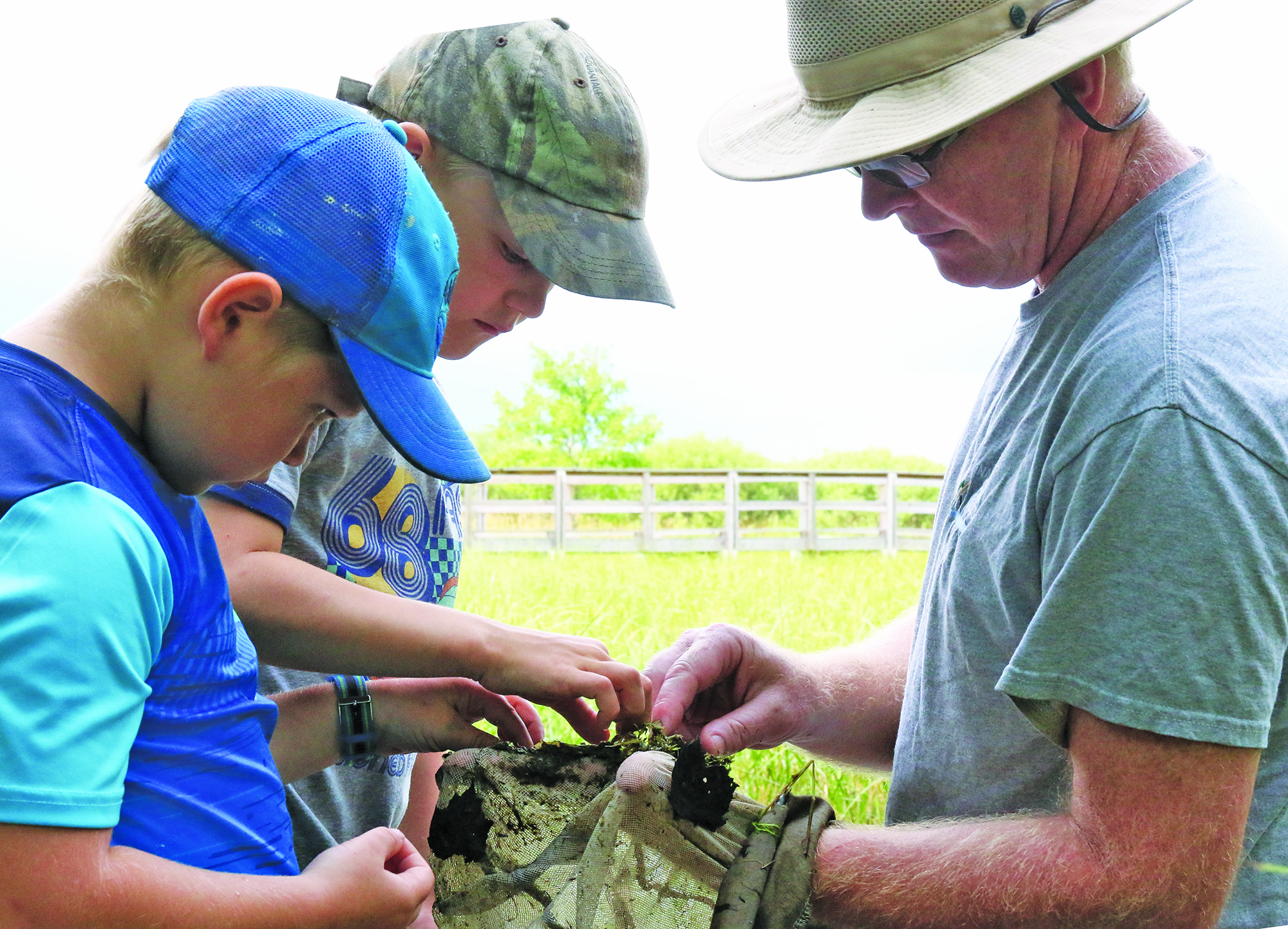 Jeremiah Hodges, left, and Evan Rankin help naturalist Tim Ewing sort through the leaves, mud, eggs, tadpoles and insects scooped from a swamp and pond area at the nature center.Carol Ryczek   NEW Media