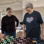"Quilt show helper Dar Borchardt, left, accepts the ""Tumbling Stars"" quilt from creator Gloria Kuhn. The quilt will be on display at the WOWSPACE for the next three weekends.