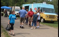 People chat and wander from food truck to food truck Sunday at the Embarrass River Campground in Tigerton, looking for something tasty to eat. The event was a first for Tigerton Main Street, which came up with the concept after having to cancel two other community events.  (Lee Pulaski | NEW Media)