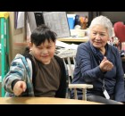 "Margaret Snow reinforces a lesson in the Menominee language with Onanahkwat Tucker in one of her language and culture classes at Keshena Elementary School. Snow reflected on the role of an elder, ""We want to pass on as much as we can, what we've learned. It's so very important because the children have to have the knowledge as it was passed down to us on how to walk the good, red road, the Native American way.""