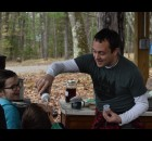 Presenter Kyle Beach gives 8-year-old Everett Rolfing an up close and personal taste of freshly processed maple syrup during the annual Maple Festival at YMCA Camp U-Nah-Li-Ya on April 10, to the delight of his sister, Malia.