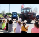 Students at Hillcrest Primary School wave excitedly April 16 as tractors driven by Shawano FFA members roll through Hillcrest's parking lot in a parade. The event was part of the Drive Your Tractor to School Day event.