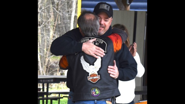 Navy veteran Shannon Flynn gets a hug from Kevin Thompson, president of Hogs for Heroes, after receiving a Harley-Davidson motorcycle from the nonprofit organization May 8 at Veterans Memorial Park in Suring.