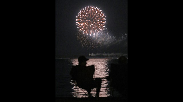 Tyler Lohmiller, Green Bay, watches the fireworks launched from the Shawano Municipal Airport from his lakeside location at the Shawano Lake County Park. Lohmiller, a Shawano native, said he is a frequent 4th of July holiday visitor to the park. Shawano's fireworks are traditionally set off on July 3.