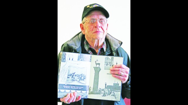 """Curtis Lienau holds a yearbook from his time on the USS Poccono AGC 16. The left-hand page shows photos from the filming of """"The Longest Day,"""" a reenactment of D-Day that happened June 6, 1944. He said he enjoyed his time on the ship and developed friendships that lasted long after. His shipmates include others from the area, including residents of Keshena, Denmark and Sheboygan.  (Carol Ryczek   NEW Media)"""