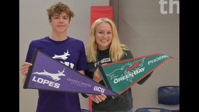 Wittenberg-Birnamwood's Wyatt Dickman, left, and McKenna Metropulos hold up flags for the colleges they will be swimming at during a signing event May 10 at the Woodson YMCA in Weston.