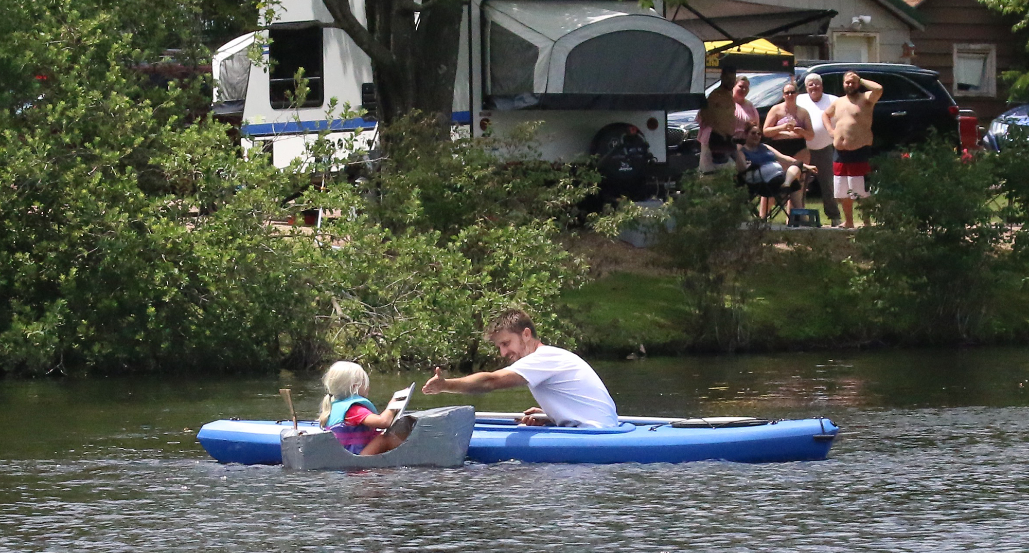 Paul Janda, who owns the Tilleda Falls Campground with Rachel Janda, waits for a high-five from Kaylie Olson as she makes the corner in her cardboard boat, while a group of spectators watches safely from the shore.Carol Ryczek | NEW Media