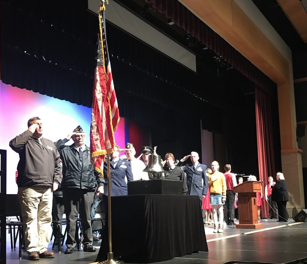 """Speakers salute the flag as Amy Thiel (background) conducts the Oconto Falls High School Vocal Jazz Ensemble in the national anthem, during the dedication program Saturday for the new community veterans monument. From left, Superintendent Dean Hess, American Legion Post 302 Commander Terris Umentum, Beverly Umentum, Vaughn Spaulding, Steve Magnin, Paula Gardipee, the Rev. Gary Olson and Madeline Maloney, a Washington Middle School student who read the poem """"I Am Your Flag."""" (Warren Bluhm   NEW Media)"""