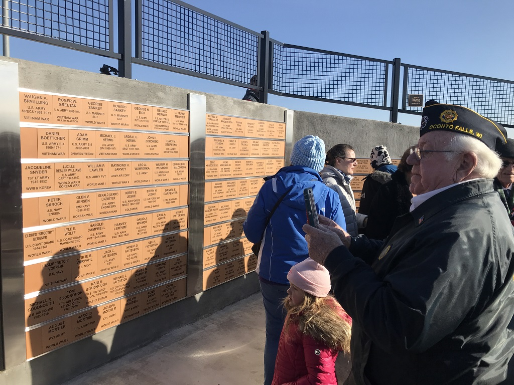 Gerald Linzmeyer, adjutant for Eick-Sankey American Legion Post 302, takes pictures of the new veterans monument after the dedication ceremony and formal flag-raising. (Warren Bluhm   NEW Media)
